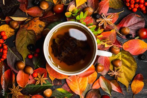Plakat Filiżanka herbata z jesień liśćmi, dokrętkami, jagodami i pikantność na nieociosanym tle ,. Niewielka głębokość pola.