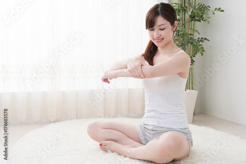 Fotografia  セルフマッサージをする女性、肘、腕