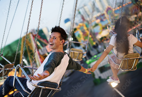 Staande foto Amusementspark Young couple riding the swings at an amusement park