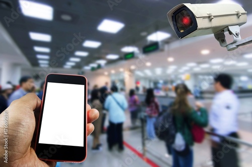 hand using mobile phone with blank screen and security camera system
