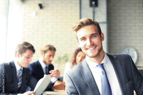 Fotografia  Businessman with colleagues in the background in office.