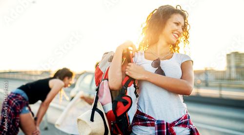 Plakat Młoda uśmiechnięta dziewczyna przygotowuje się do kontynuowania podróży biorąc jej plecak.