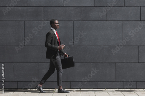 Garden Poster Fantasy Landscape Full-length portrait of handsome African American entrepreneur walking on pavement with gray block wall in background, dressed in black suit, holding leather bag and coffee cup during break in work