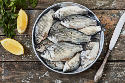 Fresh raw crucian carp fish with lemon and parsley on old wooden background Canvas Print