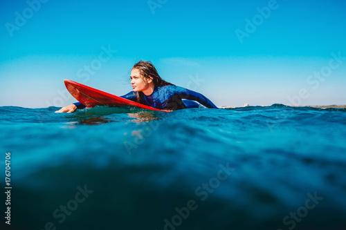 Plakat Surf girl unosi się na desce surfingowej. Kobieta w oceanie podczas surfowania. Surfer i ocean