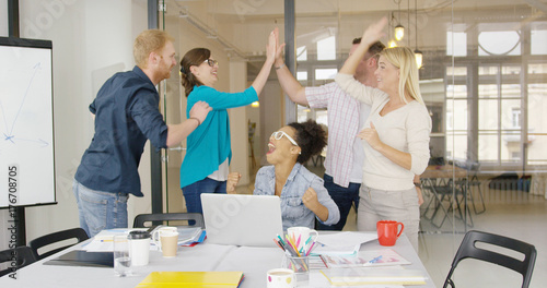 Happy and laughing coworkers giving high five while celebrating new victory and standing in modern office with table and laptop.