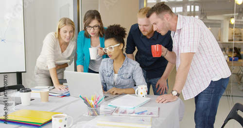 Fotografía  Young people standing around female coworker and watching laptop at table in office all together sharing ideas