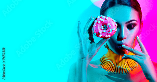 Foto op Plexiglas Beauty Fashion model woman posing in studio with donut in colorful bright lights