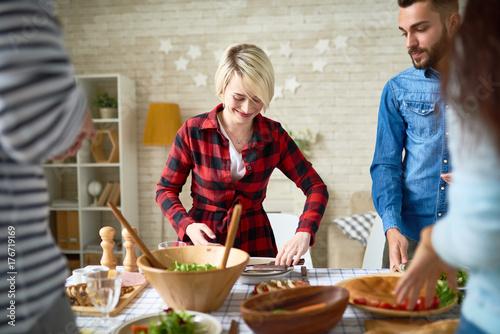 Plakat Grupa młodzi ludzie przygotowywa gość restauracji dla świątecznego świętowania wpólnie, ostrość na szczęśliwym młodej kobiety utworzenia stole