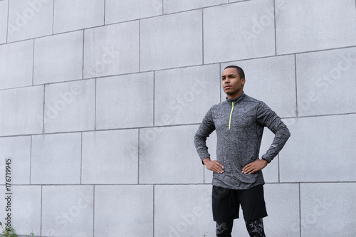 Garden Poster Fantasy Landscape Isolated cropped shot of attractive young Afro American sportsman in trendy sports clothes, standing at grey brick wall, keeping hands on his waist while relaxing after running exercise, feeling tired