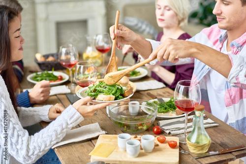 Plakat Portret cztery ludzie je przy świątecznym obiadowym stołem z wyśmienicie jedzeniem w domu, cieszący się wakacyjnego świętowanie