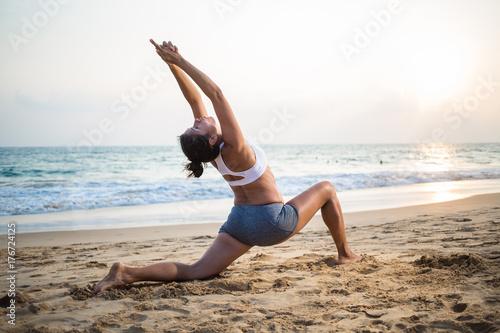 Plakat Naturalny przyglądający kobieta w ciąży ćwiczy joga przy seashore przy zmierzchem