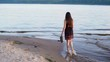 The brunette girl walks along the water along the shore.