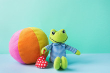 Kids Toys Small Plush Frog Holding Red Heart Multicolored Textile Soft Ball On Blue Green Background. Banner Placeholder Charity Nursery Hospital Copy Space