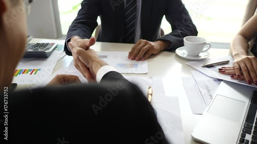 Fotografía  Mature businessman shaking hands to seal a deal with his partner and colleagues in office