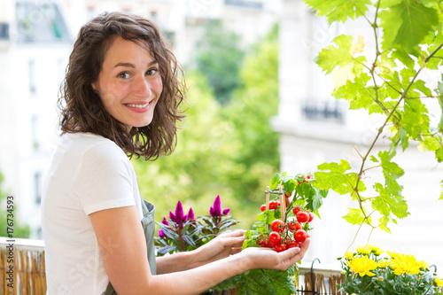 Plakat Młoda kobieta bierze opiekę jej rośliny i warzywa na jej miasto balkonu ogródzie - środowiska i ekologii temat