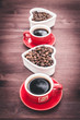 Background on a theme of coffee with place for text. Two cups of coffee, espresso, coffee beans, wooden table.