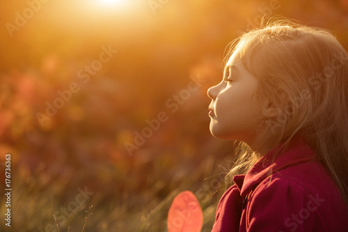 Little girl relaxing on sunset with closed eyes