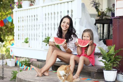Plakat Młoda dziewczyna w wiejskim domu w naturze je arbuza