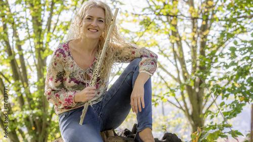 Obraz na płótnie Młoda kobieta z fletem w lesie.