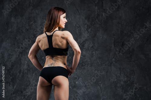 Zdjęcie XXL Ciemna kontrast fotografia tylna strona młoda piękna sprawności fizycznej kobieta z koralikami pot który trenuje w gym.