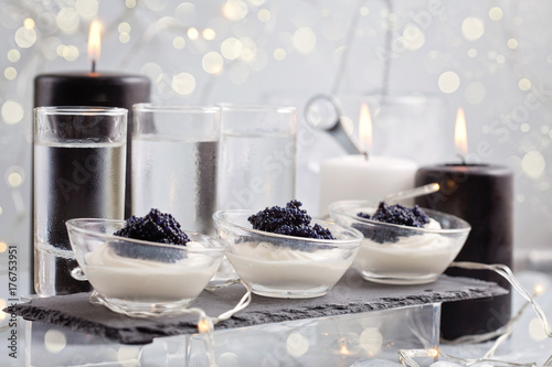 Festive buffet with vodka, black cavier and candles. Celebration concept for Christmas, new year or other party