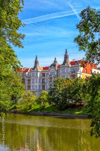 Obraz na dibondzie (fotoboard) Widok piękny historyczny budynek na rzecznym Odra banku w Wrocławskim przez zielonych drzew i gałąź nad niebieskim niebem