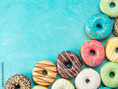 Photo Top view of assorted donuts on blue concrete background with copy space