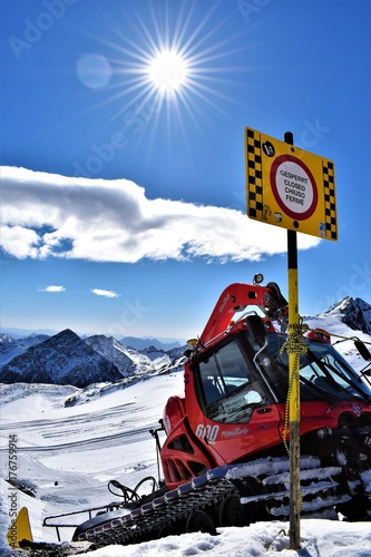 Fotografie, Obraz  A snow groomer after working on the snowpark with warning sign in the foreground