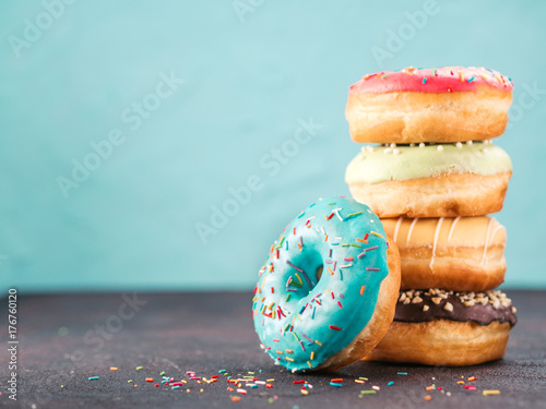Fototapeta Stack of assorted donuts on black and blue cement background