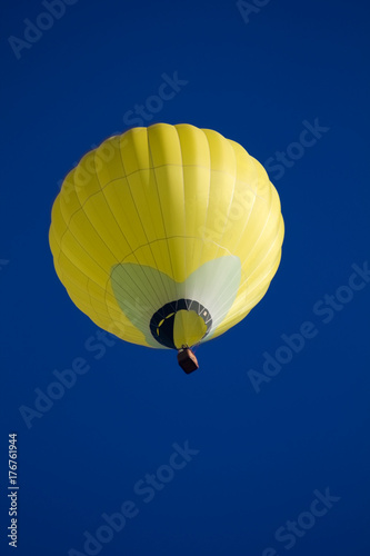 Plakat Żółty gorącego powietrza ballon na niebieskim niebie.