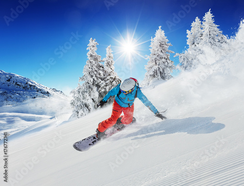 obraz dibond Young man snowboarder running down the slope in Alpine mountains