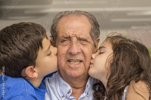 Plakat Wnuki całują ich dziadka