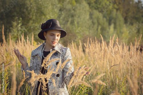 Plakat atrakcyjna młoda kobieta luksusowych spaceru na jesieni suchej trawy