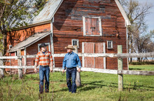 Horizontal Image Of Two Caucasian Cowboys Walking And Talking Next To A Wooden Fence With A Big Red Barn In The Background On A Ranch On A Sunny Summer Day.