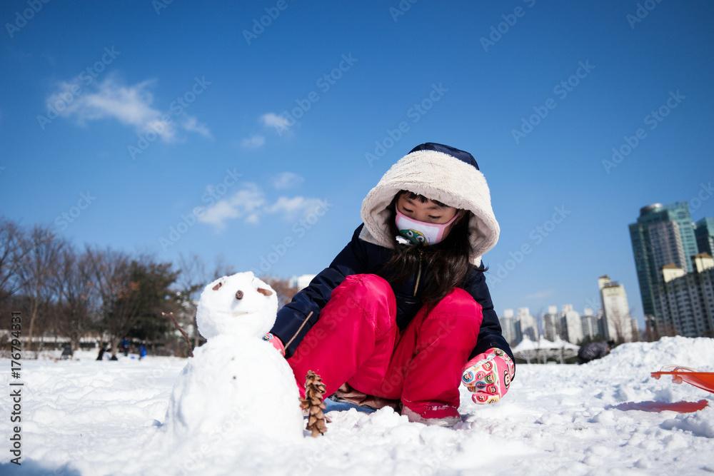 도심 공원에서 눈사람을 만들고있는 여자아이 Poster