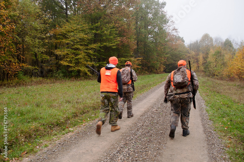 Three hunters walking a dirt road in the fall woods