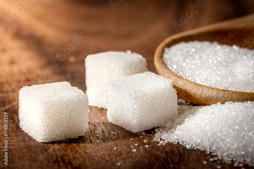Close up  sugar cubes and cane in wooden spoon on the table ,retro color tone