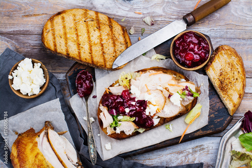 Fotomural Homemade leftover thanksgiving day sandwich with turkey, cranberry sauce, feta cheese and vegetables