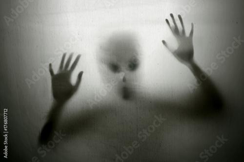 Silhouette of alien seen through sheet