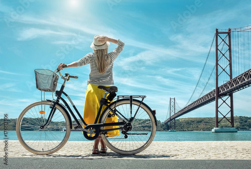 Blonde woman in summer hat and yellow skirt with her city bicycl Wallpaper Mural
