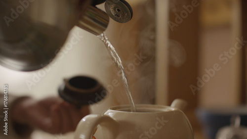 Fotografering  Woman pours boiling water into the cup and brew tea in a tea bag