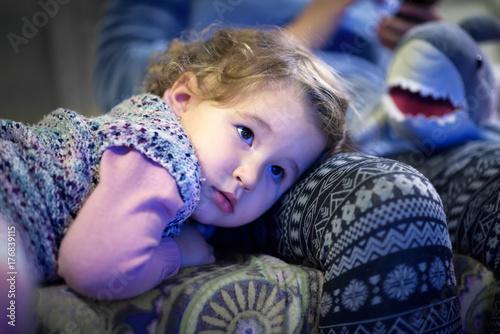 Plakat Mała dziewczynka ogląda telewizję w domu
