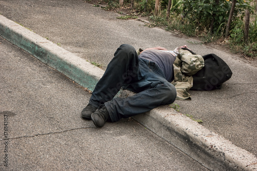 Obraz Unconscious drunk man. Person lying in the street. Health problems of the homeless. - fototapety do salonu