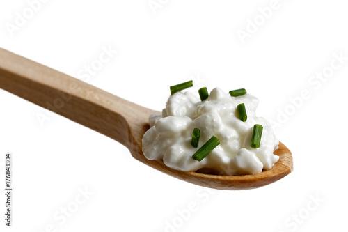 Plakat Klockowaty chałupa garnirujący z szczypiorkami na drewnianej łyżce odizolowywającej na bielu.