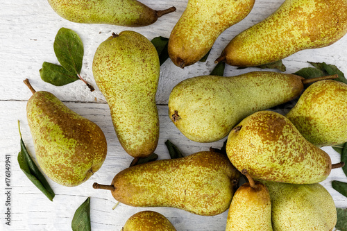 Abate fetel pears with leaves on white painted wood from above. Canvas Print