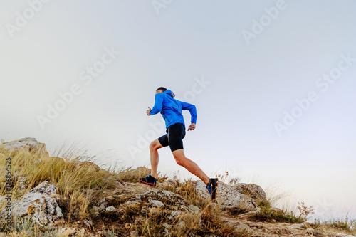 Zdjęcie XXL bieganie pod górę na kamienie mężczyzna sportowiec biegacz widok z boku