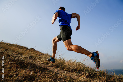 Fotografiet  dynamic running uphill on trail male athlete runner side view