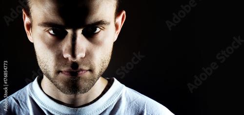 Fotografie, Tablou  man on dark background looks at camera, dark low key portrait