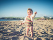 Little baby on beach pointing